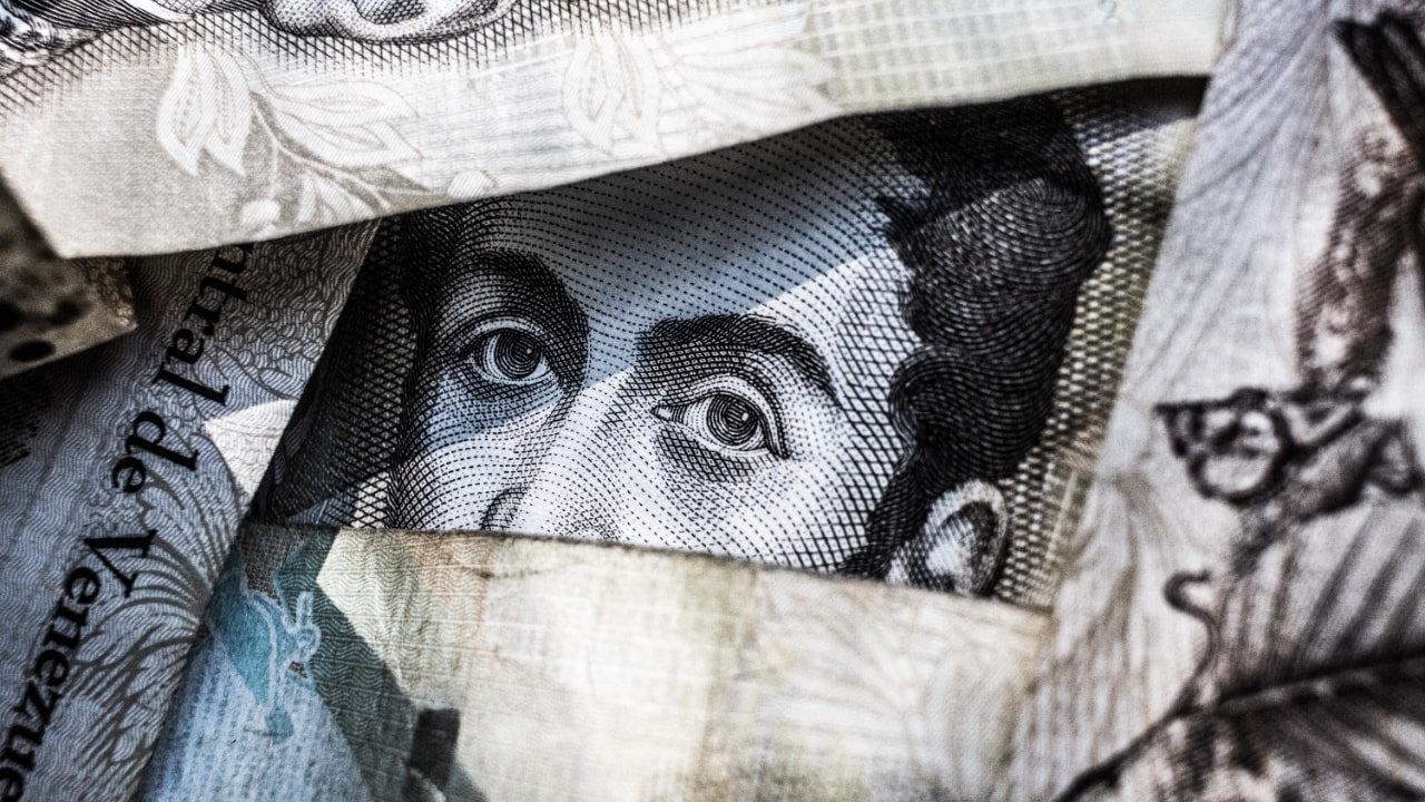 Human eyes peeking through a bunch of currency notes
