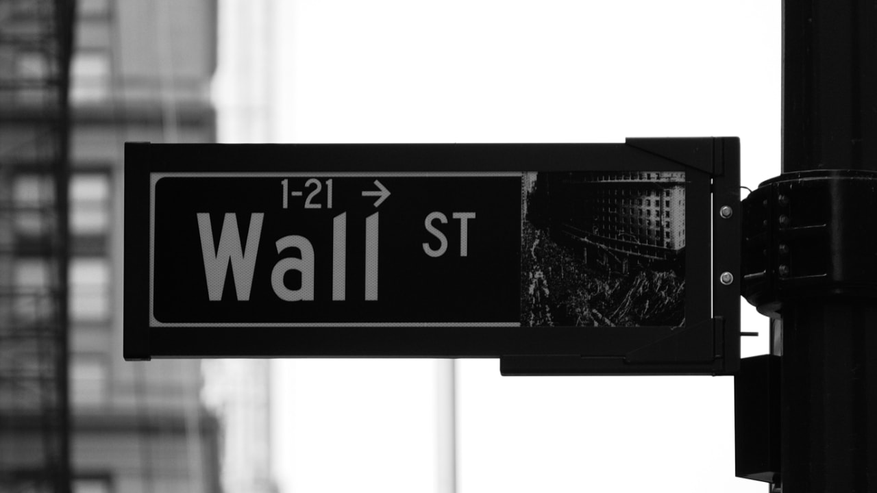 Close-up view of a wayfinding signage showing direction to Wall Street